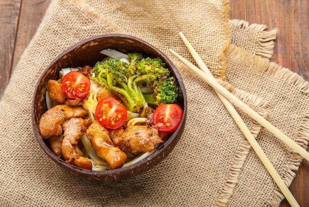 Udon mit fleisch und gemüse in yakiniku-sauce in einem teller mit kokosnussschalen auf einem holztisch