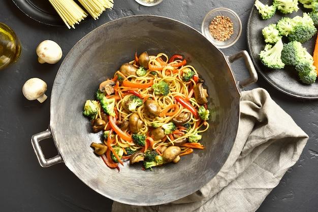 Udon nudeln mit gemüse im wok anbraten