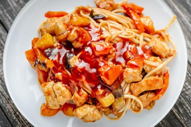 Udon nudeln mit hähnchen und gemüse in süß-saurer sauce anbraten. traditionelle asiatische küche