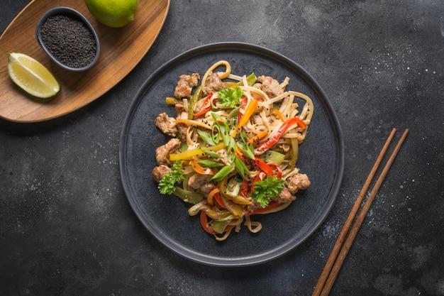 Udon pfannennudeln mit gemüse und schweinefleisch. asiatische küche.