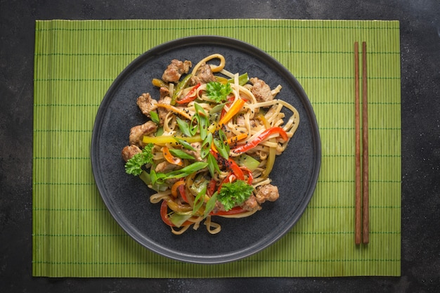 Udon pfannennudeln mit schweinefleisch und stäbchen braten. asiatische küche.