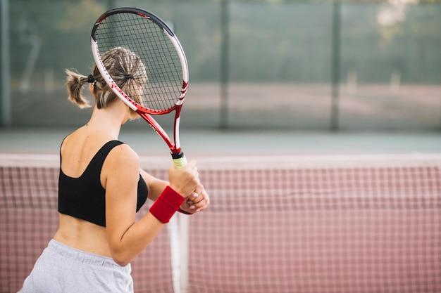 Üben des weiblichen tennisspielers der seitenansicht
