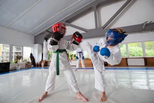 Üben von kampfkünsten. zwei jungen im weißen kimono üben kampfkünste mit helmen und handschuhen