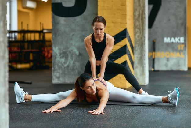 Üben von querfäden. junge flexible frau sitzt auf yogamatte im fitnessstudio und macht dehnübungen mit hilfe eines weiblichen personal trainers im fitnessstudio. sport und gesundes lifestyle-konzept