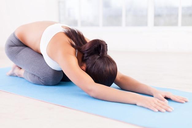 Üben von yoga. schöne junge frau, die auf yogamatte ausdehnt