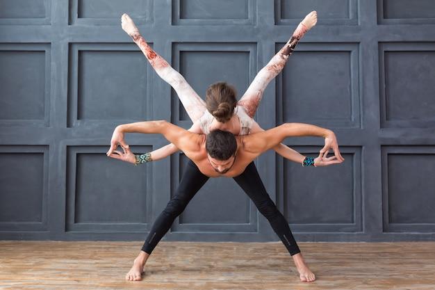 Übende acro yogahaltungen des paares