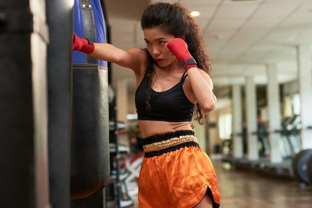 Übende durchschläge des weiblichen boxers auf sandsack in einer turnhalle