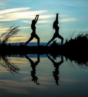 Übende yogahaltung der frau bei sonnenuntergang
