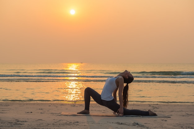 Übende yogahaltung der jungen gesunden yogafrau auf dem strand bei sonnenaufgang