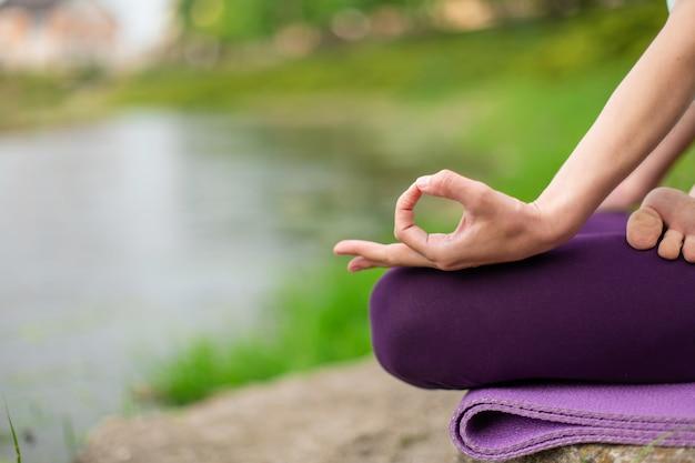 Übende yogalektion der yogafrau, atmung, meditation, übung ardha padmasana tuend, halbe lotoshaltung mit mudra geste, nahaufnahme im sommer auf natur gegen des wassers