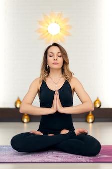 Übende yogameditation der jungen frau in der turnhalle