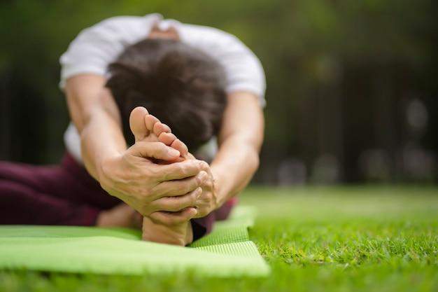 Übende yogaübung der älteren asiatin im freien morgens. senior gesunden lebensstil