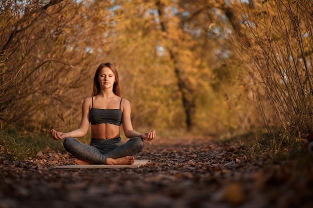Übende yogaübung der jungen frau am herbstpark mit gelben blättern. sport und freizeit lifestyle