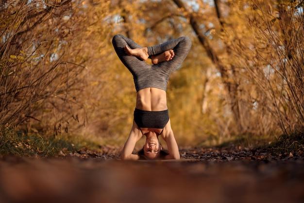 Übende yogaübung der jungen frau am herbstpark mit gelben blättern