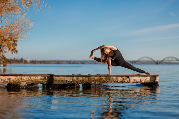 Übende yogaübung der jungen frau am ruhigen hölzernen pier mit stadt. sport und erholung in der großstadt