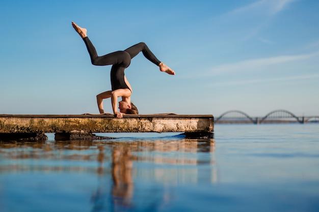 Übende yogaübung der jungen frau am ruhigen hölzernen pier mit stadt sport und erholung in der stadteile
