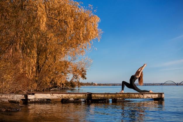 Übende yogaübung der jungen frau am ruhigen hölzernen pier mit stadthintergrund. sport und erholung in der großstadt