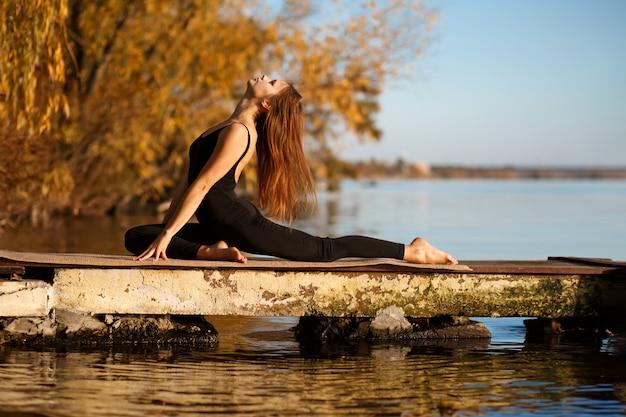 Übende yogaübung der jungen frau am ruhigen pier im herbstpark