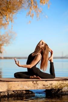 Übende yogaübung des jungen mädchens am ruhigen pier im herbstpark
