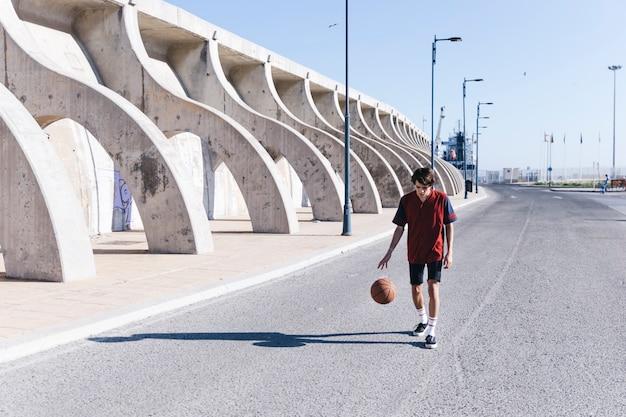 Übender basketball des spielers auf straße in der stadt