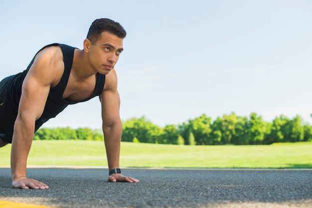 Übender sport des athletischen mannes im freien
