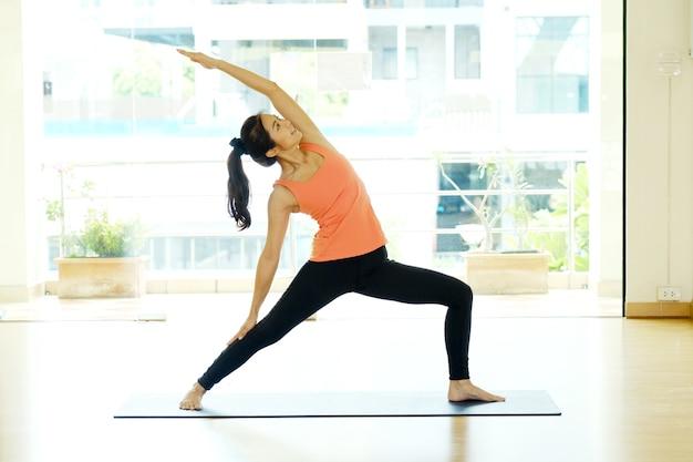 Übender yoga-innenstudiohintergrund der jungen asiatischen frau