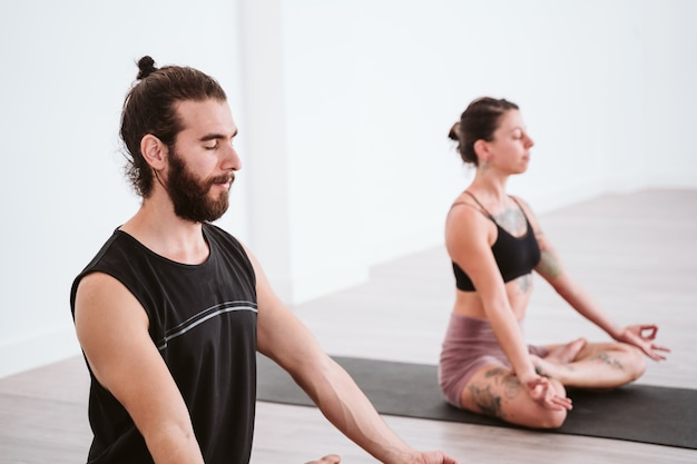 Übender yogasport des jungen mannes und der frau an der turnhalle