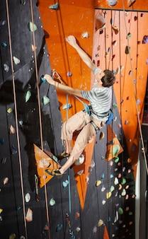 Übendes auf felsenwand zuhause klettern des männlichen kletterers
