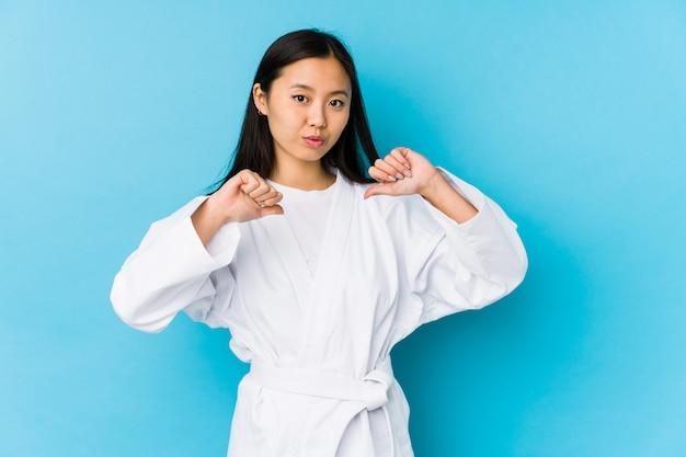 Übendes karate der jungen chinesischen frau lokalisiert fühlt sich stolz und selbstbewusst, beispiel zu folgen.