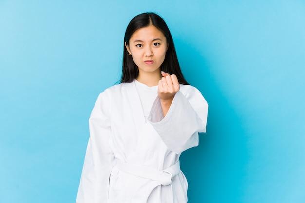 Übendes karate der jungen chinesischen frau lokalisierte das zeigen der faust zur kamera, aggressiver gesichtsausdruck.