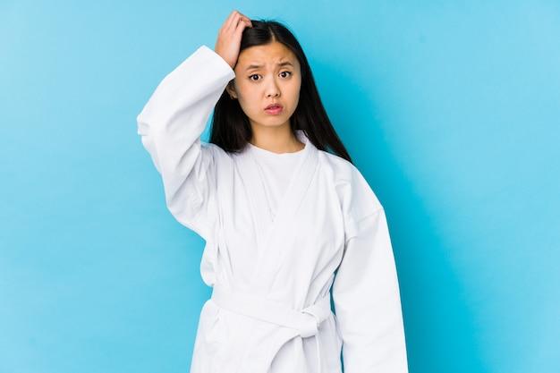 Übendes karate der jungen chinesischen frau lokalisierte, entsetzt seiend, sie hat sich an wichtige sitzung erinnert.