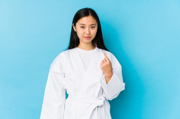 Übendes karate der jungen frau, das mit dem finger auf sie zeigt, als ob einladung näher kommen.