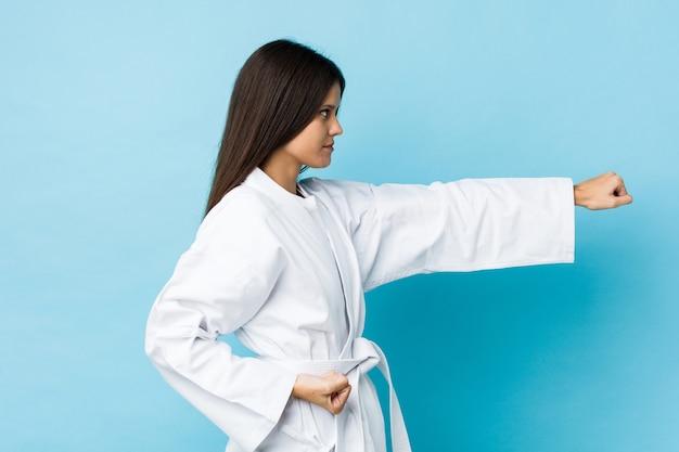 Übendes karate der jungen kaukasischen frau lokalisiert auf einer blauen wand