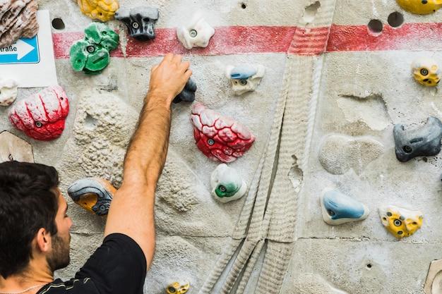 Übendes klettern des mannes auf künstlicher wand zuhause. aktiver lebensstil und boulderkonzept.