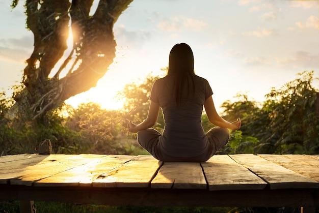 Übendes meditationsyoga der frau auf der natur bei sonnenuntergang.