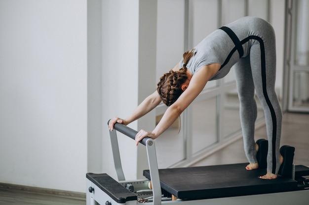 Übendes pilates der frau in einem pilates reformer