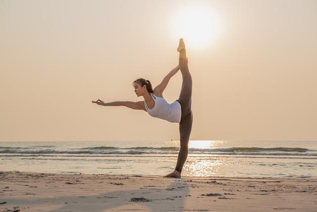 Übendes und trainingsyoga der jungen gesunden frau auf dem strand bei sonnenaufgang