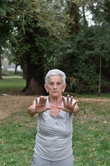 Übendes yoga der älteren frau draußen