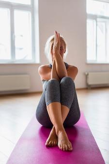 Übendes yoga der älteren frau in der sportkleidung