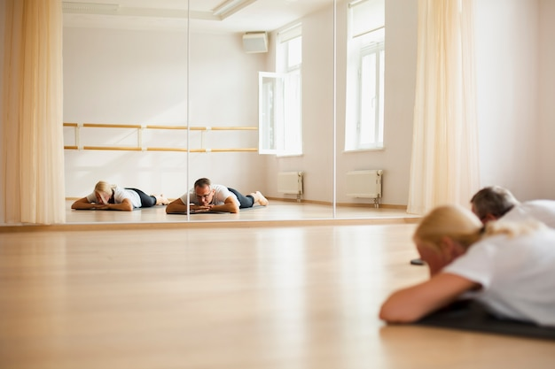 Übendes yoga der älteren paare zusammen