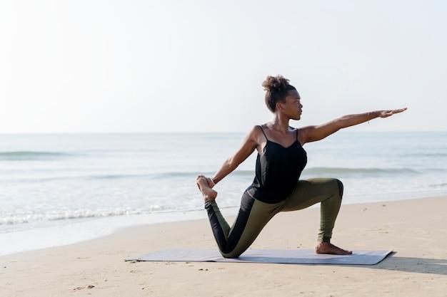 Übendes yoga der afroamerikanerfrau am strand