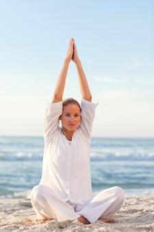 Übendes yoga der aktiven frau am strand