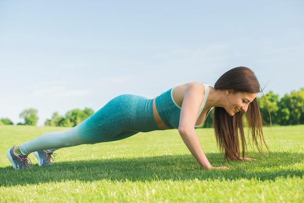 Übendes yoga der athletischen frau im freien