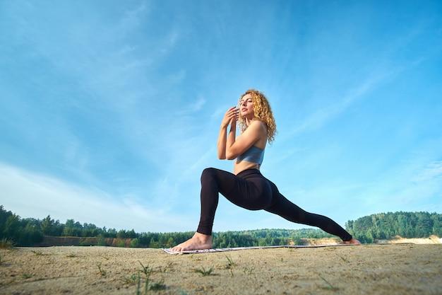 Übendes yoga der attraktiven gelockten frau der rothaarigen draußen