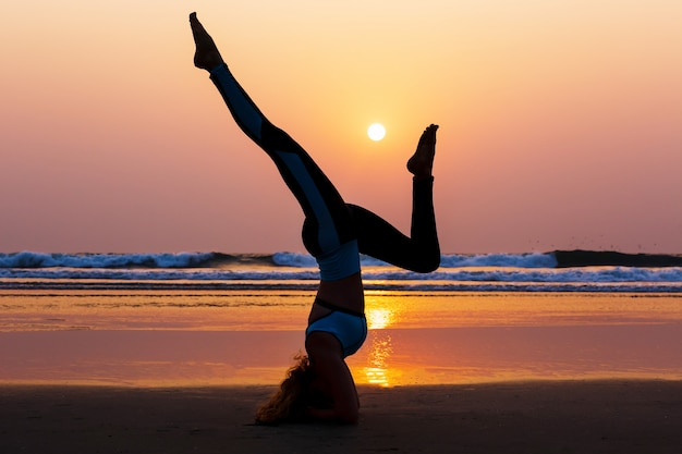 Übendes yoga der frau auf dem strand bei sonnenuntergang