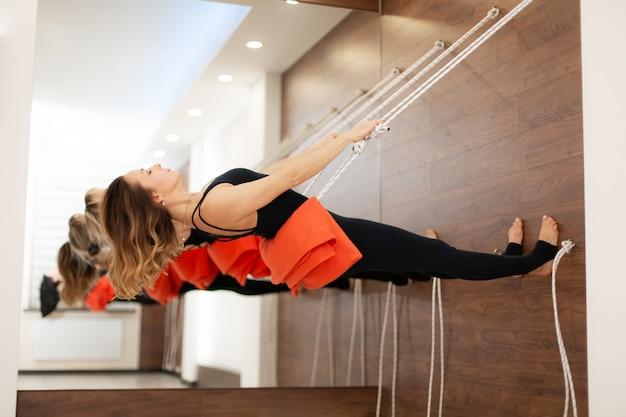Übendes yoga der frau auf den seilen, die in turnhalle ausdehnen. fit und wellness lifestyle