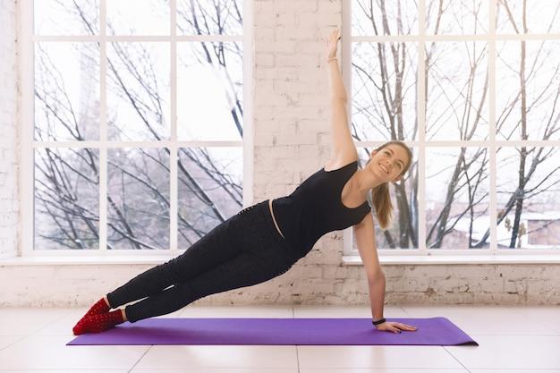 Übendes yoga der frau, das die seitenplanke zu hause sich lehnt auf einem arm im hellen raum auf yogamatte tut. sich warm laufen