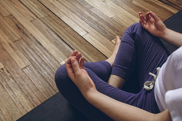 Übendes yoga der frau, das halbe lotus-haltung mit mudra tut