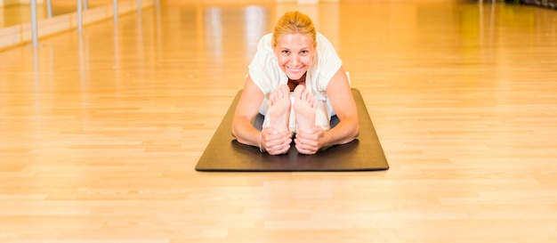 Übendes yoga der frau, das in paschimottanasana-position sitzt