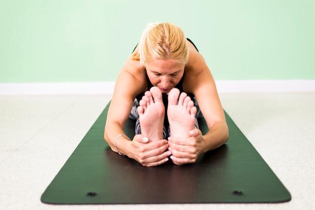 Übendes yoga der frau, das in position paschimottanasana (sitzrumpfbeuge) auf boden sitzt